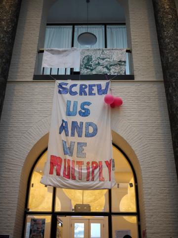 """""""打擊我們,我們就會倍數增加""""的標語高掛在Maagdenhuis的大廳裏,宣示學生非達成訴求目標不可的決心。"""