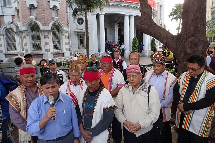 長老教會牧師歐蜜偉浪(持麥克風者)在監察院前帶領族人禱告。
